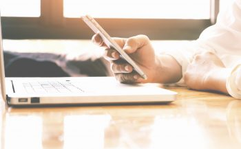 Hand of businessman using smartphone and laptop for analyze business information. Vintage tone, Retro filter effect, Soft focus, Low light.(selective focus)